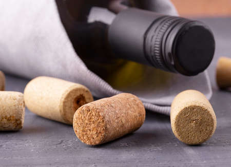 Glass bottle of white wine with corks on wooden table background