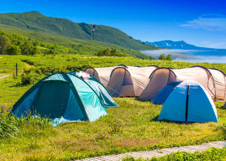 Camping tent in campground at national park. Tourists camped in the woods on the shore of the lake on the hillside. Banco de Imagens