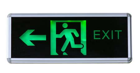 Illuminated green emergency exit sign Stock Photo
