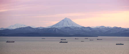 The fishing boats in the Bay with the volcano on Kamchatka
