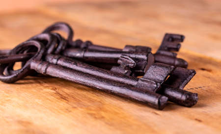 Old key on the wooden background Фото со стока
