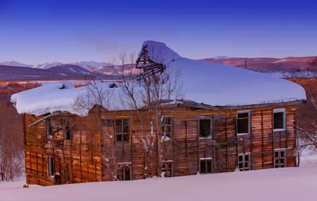The old ugly dilapidated wooden house on the  sunset Imagens