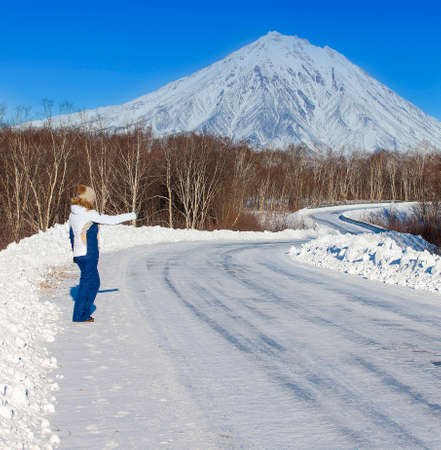 The girl hitchhiking on the winter road opposite the volcano