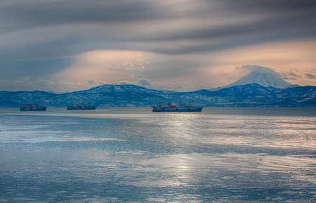 Drei große Fischerboote vor dem Hintergrund von Hügeln und Vulkanen Standard-Bild