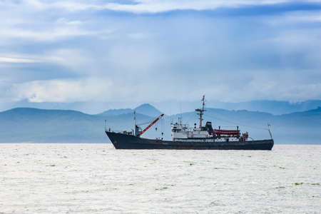 large fishing vessel on the background of hills and volcanoes Banque d'images