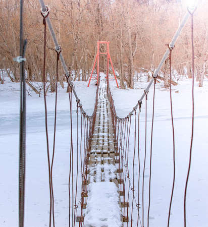 old suspension bridge across river, winter fir forest in snow