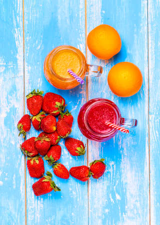 grapefruit and orange juice, strawberries and orange on a blue table