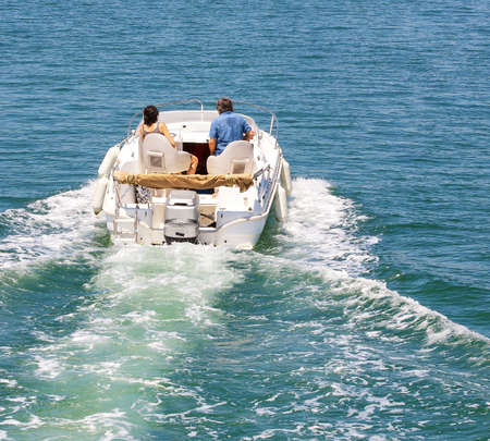 Motor boat with married couple at in sea landscape