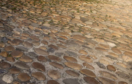 The old stone pavement illuminated by the sun Imagens
