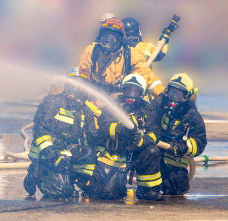 firefighters with hose extinguish a fire