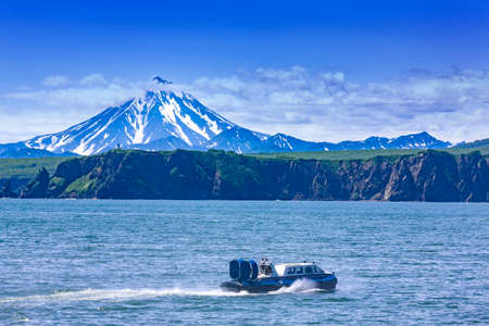 Hovercraft on Pasific ocean in kamchatka Peninsula on the background volcano