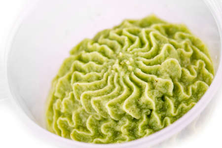 plastic container wasabi sauce on white background