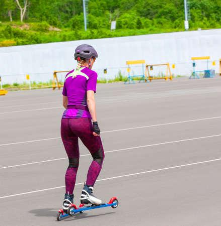 The girl sportswoman rides on the roller skis on the asphalt