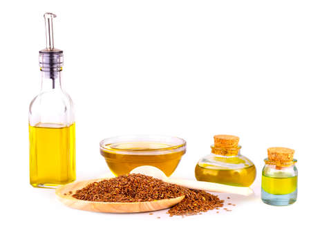Linseed oil,  bowl of linseeds and wooden spoon  on white background