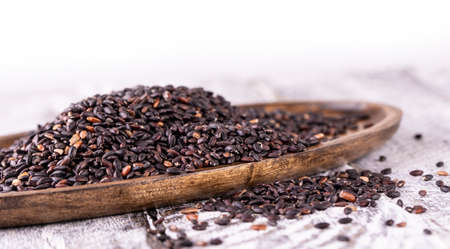Wooden plate with black rice on old wooden background