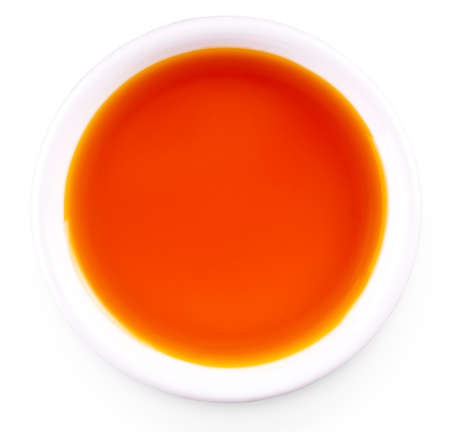 sea buckthorn oil in the white small Cup isolated on white background Imagens