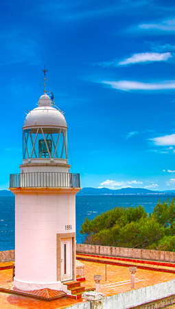 Roses lighthouse against blue sky with white clouds on northern coast Spain Imagens