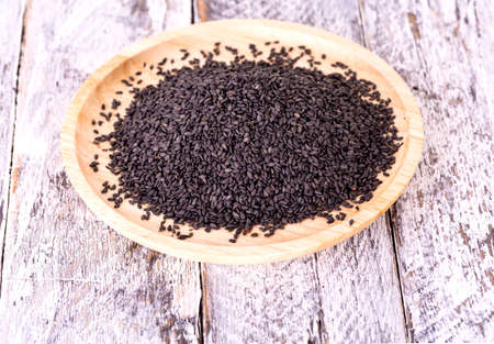 Close up of black sesame seed on wooden plate Stock Photo
