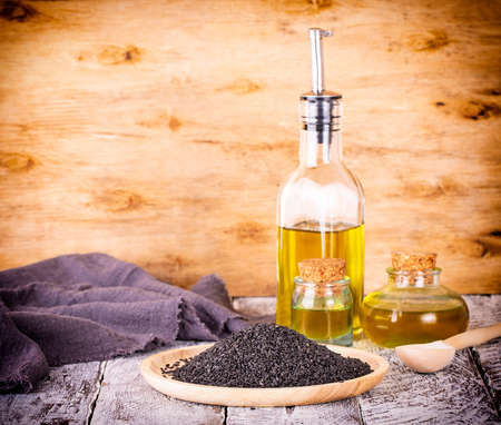black sesame and oil on old wooden background Stock Photo