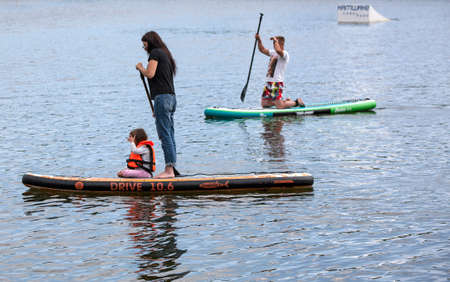 kamchatka, Russia 02 August 2019: Men and women with her baby stand up paddle boarding (sup) on lake in recreation center Blue Loguna in Kamchatka