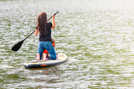 Girl with her baby stand up paddle boarding (sup)