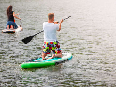 Men and women with her baby stand up paddle boarding (sup)