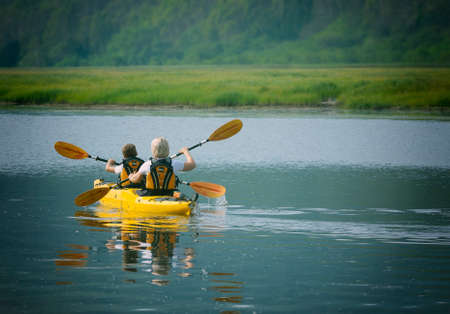 woman with a child on the lake and ride on kayak Stock Photo