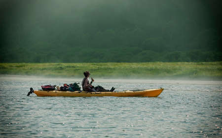 Young woman on kayak on the Lake with copy space. Banco de Imagens