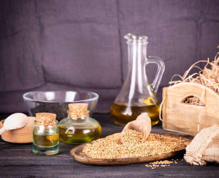 Sesame oil in glass and seeds on lod wooden background