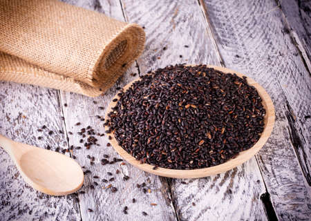 Black rice on the old wooden background
