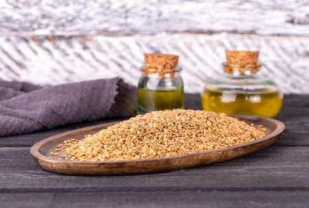 Sesame oil in glass and seeds on wooden background Banco de Imagens