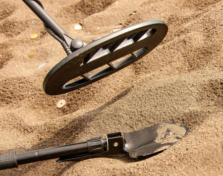 Metal detector, ring and spade on the sand