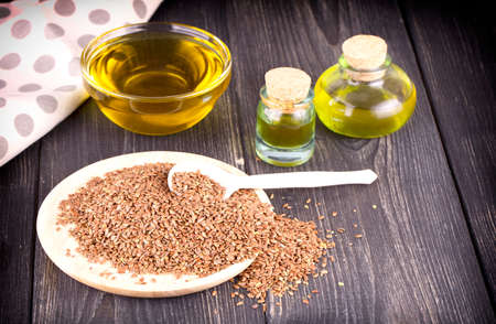 Sesame oil in glass and seeds on wooden background Stock fotó