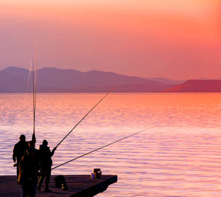 The fishermanes silhouette fishing at sunset on the see