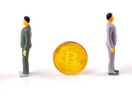 Close up of two businessman miniature figure standing near the bitcoin coin. Business, e-commerce, finance and technology concept
