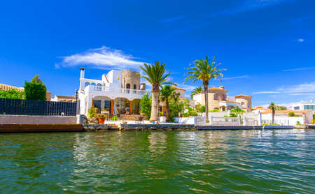 The house with palm by the water at the resort in Spain