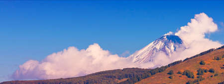 The Panoramic view of snow volcano and blue sky