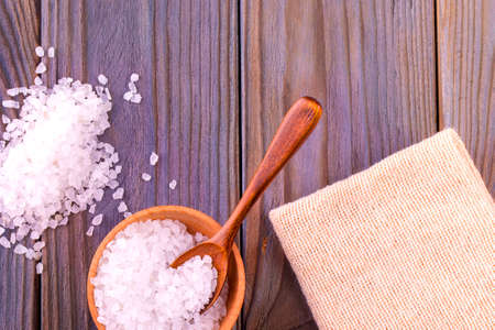 The white sea salt on cup,  spoon and  burlap on a wooden table