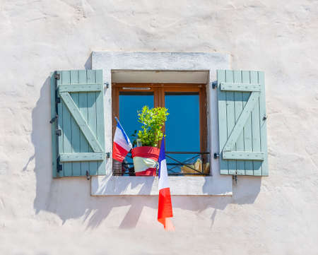 The facade of the building with the flags of France in the window.