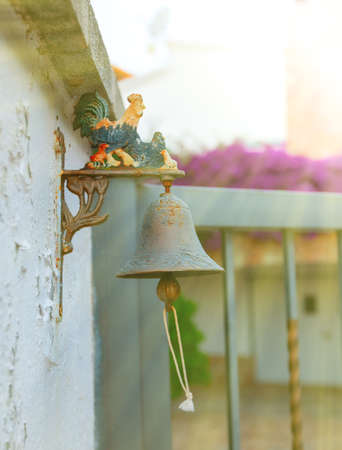 The Small iron bell with colored rooster outside the house.