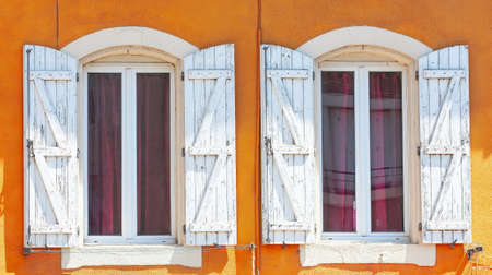 The Detail of an open wooden vintage rustic windows on red cement old wall can be used for background. White window shutters