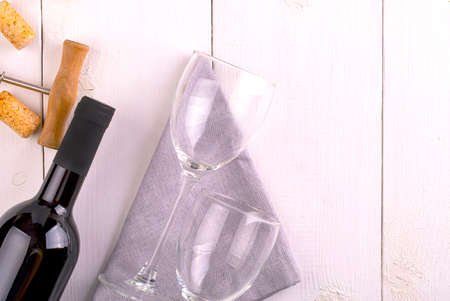 two empty glasses, bottle of red wine and corkscrew on white wooden surface Stock fotó