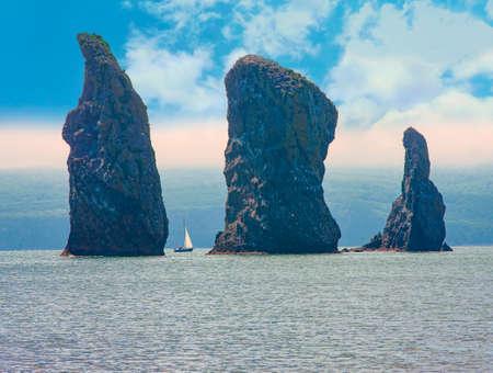 The Sailboat sails near the coast and rocks on Kamchatka Peninsula