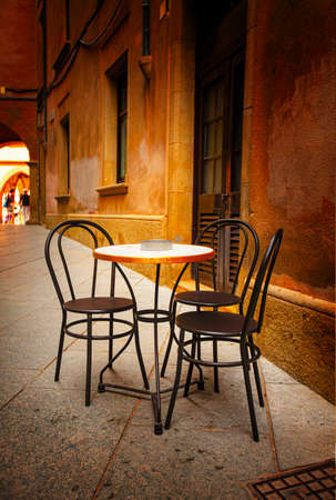 The table and chairs in the street outdoor cafe. Selective focus