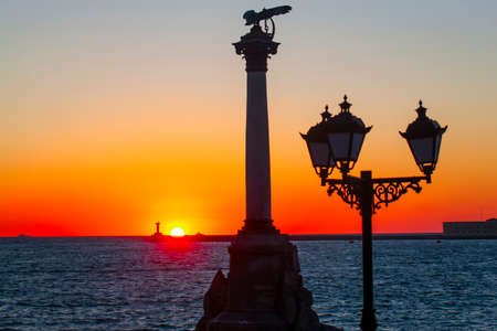 The sunset on the embankment of Sevastopol. The symbol of Sevastopol is a Monument to sunken ships, a historical memorial.