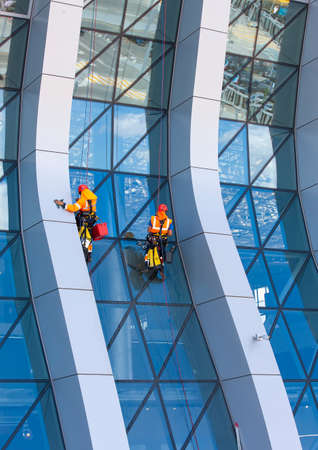 The window cleaner working on a glass facade modern skyscraper