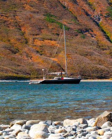 The north yacht on the bay of Pacific ocean in Kamchatka peninsula with mountains on background