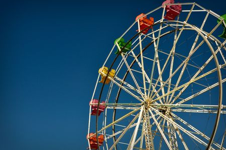 wheel spin: Exciting red, pink, yellow ferris wheel Stock Photo