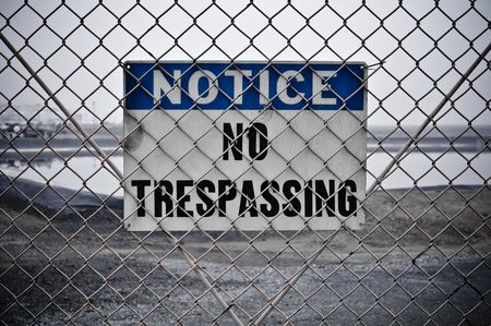 Dingy No Trespassing Sign in Front of Protected Area Stock Photo - 6119601