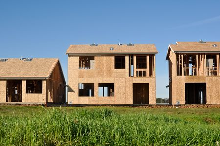 residential construction: Three Homes Under Construction with Blue Sky